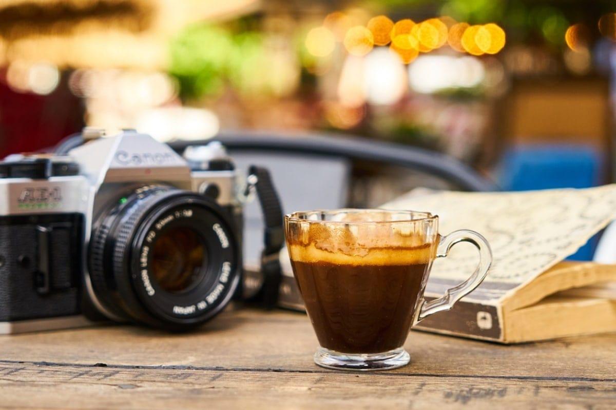 Canon AE 1 na stole, káva a kniha.
